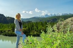Young blonde woman stay on a rock on a sunny warm autumn summer royalty free stock photo