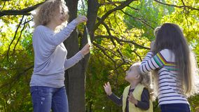 Young blonde woman staying in the sunny park and blowing soap bubbles. Her two little pretty daughters running around. Trying to catch bubbles. Joyful caucasian stock video