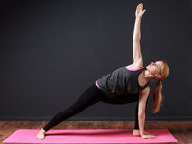 Young blonde woman staying triangle pose Royalty Free Stock Photos