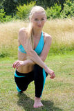 Young blonde woman stretching her legs on the grass in the park Royalty Free Stock Photo