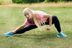 Young blonde woman stretching her legs in the park Stock Photos