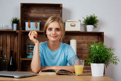 Young blonde woman studying for university home Stock Photo