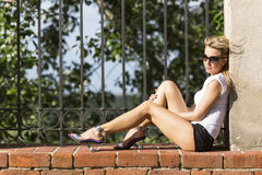 Young  blonde woman in sun glasses and shorts sitting in the Park on a brick wall. Stock Images