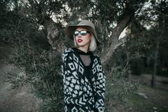 Portrait of blonde woman exploring nature in front of an olive tree. Young blonde woman with sunglasses, hat, and red lips enjoying discovering the forest Stock Images