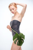 Young blonde woman in swimsuit posing with green leaf, skincare concept. Sensual young blonde woman in swimsuit posing with green leaf, skincare concept Royalty Free Stock Image
