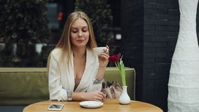 Young blonde woman takes a cup of coffee to her lips sitting at the table in cafe stock video