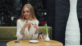 Young blonde woman takes a cup of coffee to her lips sitting at the table in cafe stock footage