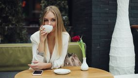Young blonde woman takes a cup of coffee to her lips sitting at the table in cafe stock video footage