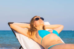 Young blonde woman takes sunbathing Royalty Free Stock Image