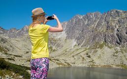 Young blonde woman taking photographs of lake and mountain Stock Photos