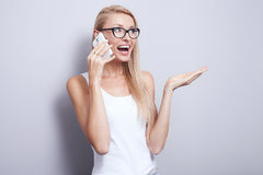 Young blonde woman talking by mobile phone. Royalty Free Stock Photos