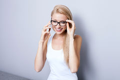 Young blonde woman talking by mobile phone. Royalty Free Stock Images