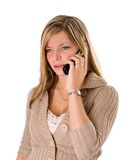 Young blonde woman talking on phone frowning. Portrait of a beautiful young blonde woman talking on the phone looking angry on a white background Royalty Free Stock Photography