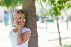 A young blonde woman talking on a phone in a park royalty free stock image