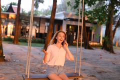 Young blonde woman talking by smartphone and sitting on swing, sand in background. stock photo