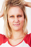 Young blonde woman tearing her hair Stock Photo