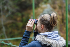 Young blonde woman tourist on a cliff looking through binoculars Stock Photos