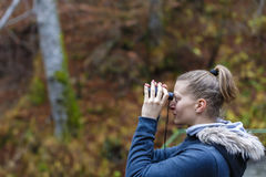 Young blonde woman tourist on a cliff looking through binoculars Stock Photo