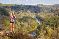 Young blonde woman tourist   on a cliff taking pictures of the a Royalty Free Stock Image