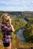 Young blonde woman tourist   on a cliff taking pictures of the a Royalty Free Stock Photography