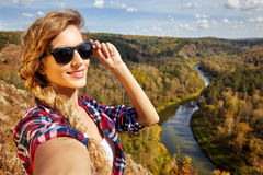 Young blonde woman tourist  on a cliff taking selfie picture on Royalty Free Stock Photography