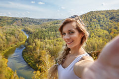 Young blonde woman tourist  on a cliff taking selfie picture on Stock Photo