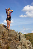 Young blonde woman tourist  in shirt and shorts  on a cliff on b Royalty Free Stock Photography