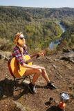 Young blonde woman tourists with guitar on cliff over river and Royalty Free Stock Photography
