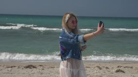 Young blonde woman in a translucent white dress and denim jacket makes a photo on the phone on the background of the sea. Her hair fluttering in the wind Slow stock footage