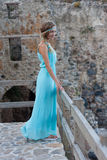 Young blonde woman in turquoise dress with braided hair against royalty free stock images