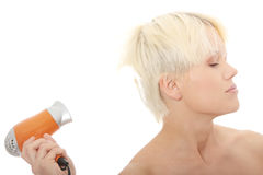 Young blonde woman using hair drier Royalty Free Stock Photo