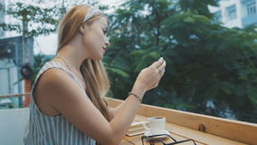 Young blonde woman using smartphone in cafe. Female write massege on mobile phone. stock video