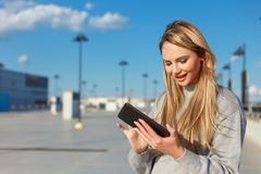 Young blonde woman using tablet outdoors. Airport or mall Stock Image