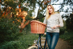 Young blonde woman on a vintage bicycle. In the countryside. Selective focus. Grain added for best impression Stock Images