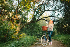 Young blonde woman on a vintage bicycle. In the park. Hipster style Stock Photography