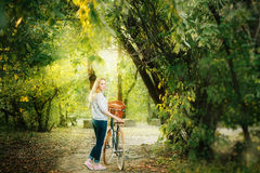 Young blonde woman on a vintage bicycle. In the park in sunset. Selective focus Royalty Free Stock Photos