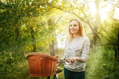 Young blonde woman on a vintage bicycle. Young blonde smiling woman on a vintage bicycle in the park in sun light. Selective focus Stock Images