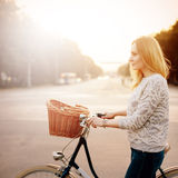Young blonde woman on a vintage bicycle. In the sunset. Image toned in instagram style. Selective focus Stock Images