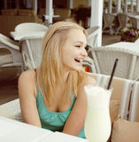 Young blonde woman waiting for her friend in white summer open cafe, happy smiling lifestyle people Royalty Free Stock Images