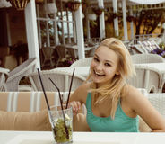 Young blonde woman waiting for her friend in white summer open cafe, happy smiling lifestyle people Royalty Free Stock Photo