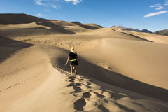 Young blonde woman walking on the Great Sand Dunes Royalty Free Stock Image
