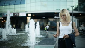 Young blonde woman walks in the city passes near the fountain, wets her hands, touches the water. stock footage