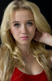 Young blonde woman wearing earrings and pendant. A closeup portrait of young beautiful blonde wearing earrings and pendant Stock Image