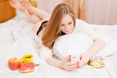 Young blonde woman wearing lingerie using mobile Royalty Free Stock Photo