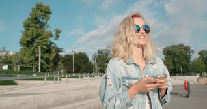 Young blonde woman wearing sunglasses using phone during sunny day in a city. Beautiful young woman typing on phone during sunny day Royalty Free Stock Photography