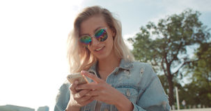 Young blonde woman wearing sunglasses using phone during sunny day in a city. Beautiful young woman typing on phone during sunny day Royalty Free Stock Image