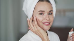 Woman with towel on head applies moisturizer cream on her face, close up