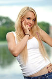 Young blonde woman in white tank top and jeans Royalty Free Stock Photography