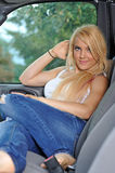 Young blonde woman in white tank top and jeans. Beautiful young blonde woman in white tank top and jeans taking shelter from the rain in the cab of a pick up Royalty Free Stock Images
