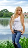 Young blonde woman in white tank top and jeans Royalty Free Stock Photos